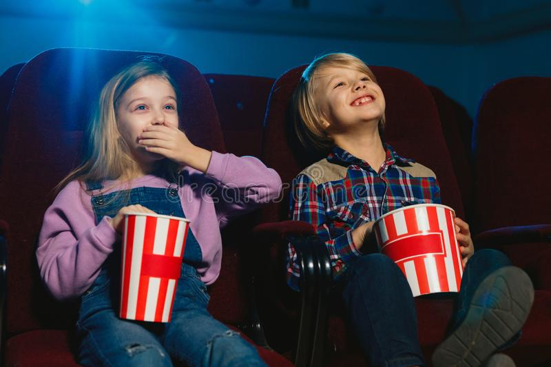Little girl and boy watching a film at a movie theater royalty free stock photos
