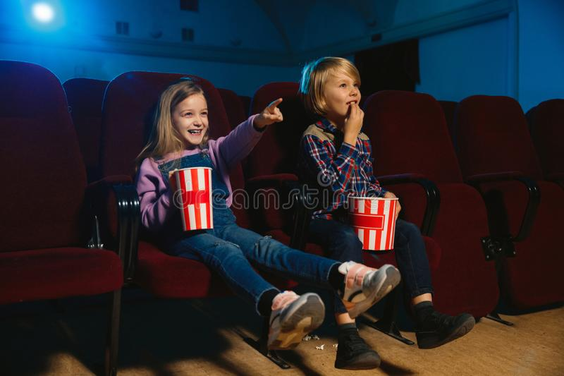 Little girl and boy watching a film at a movie theater royalty free stock image