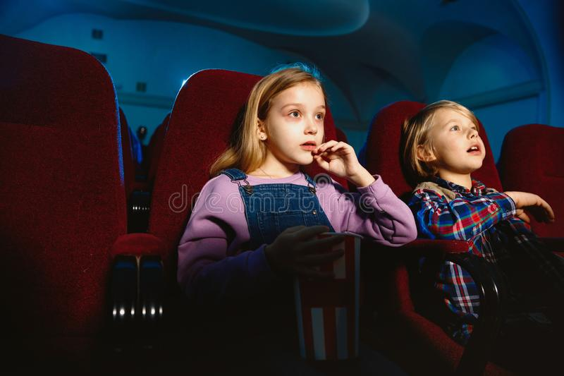 Little girl and boy watching a film at a movie theater royalty free stock images