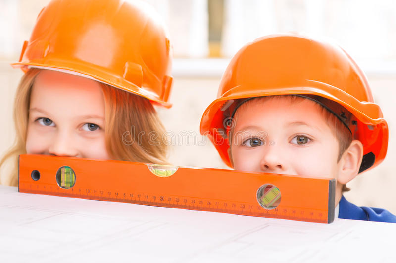 Little girl and boy are hiding behind big ruler royalty free stock image