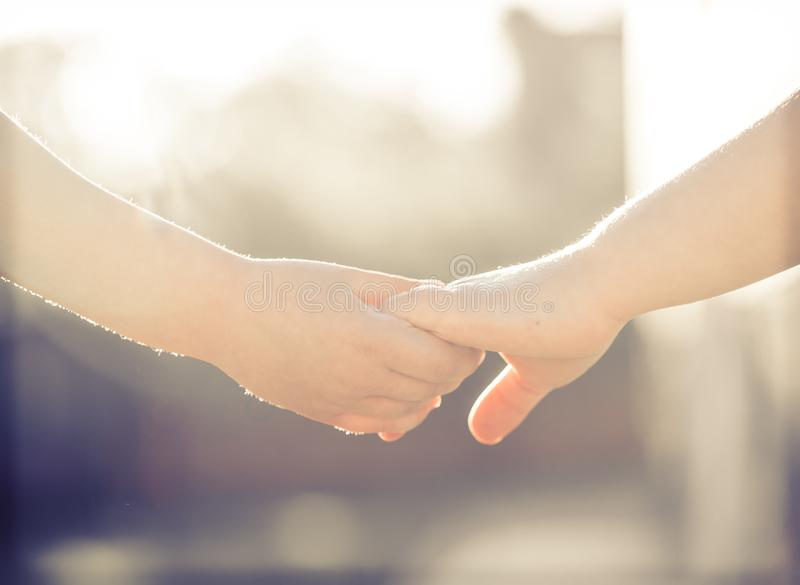 Little girl and boy hold hands close-up, against the backdrop of stock photography