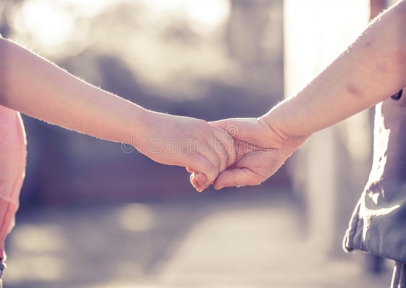 Little girl and boy hold hands close-up, against the backdrop of royalty free stock photos