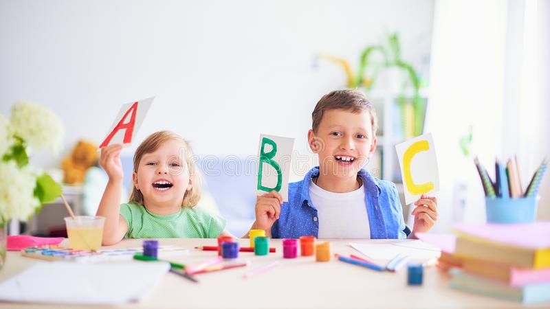 A little girl and a boy learn at home. happy kids at the table with school supplies smiling funny and learning the alphabet in a stock photography