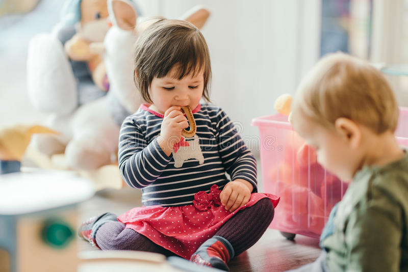 Little girl and boy playing with toys by the home stock photo