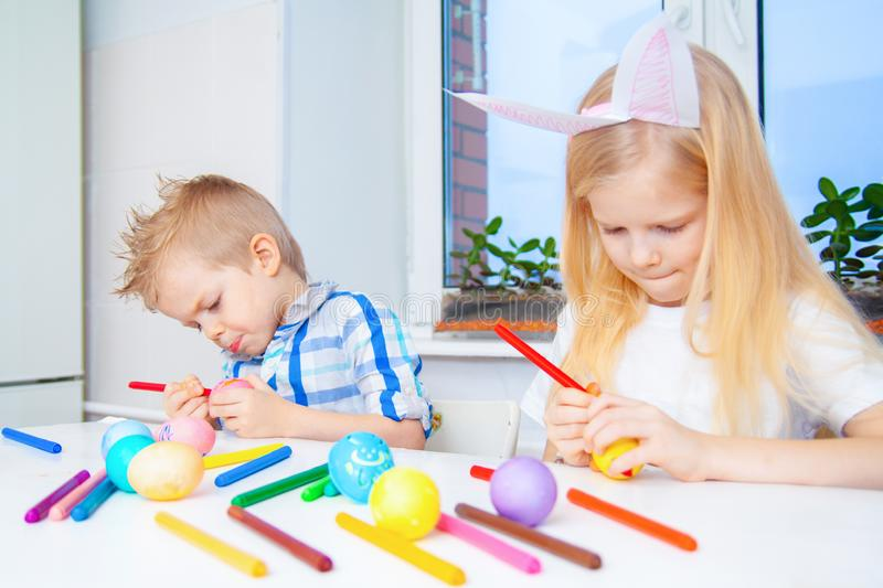 Little girl and boy in rabbit bunny ears on head are preparing for Easter and painting eggs. Colorful markers. Easter, family and stock photography