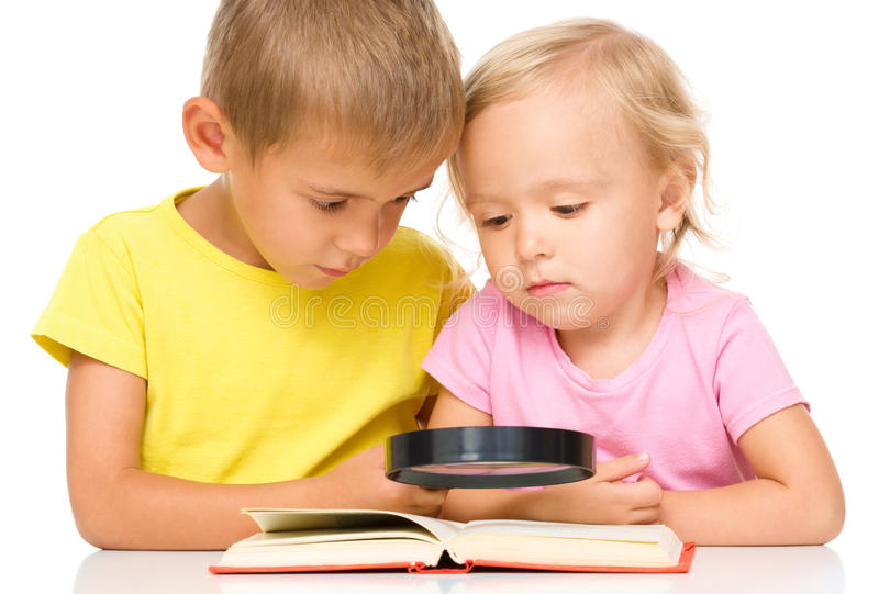 Little girl and boy are reading book. Using magnifier, isolated over white royalty free stock images