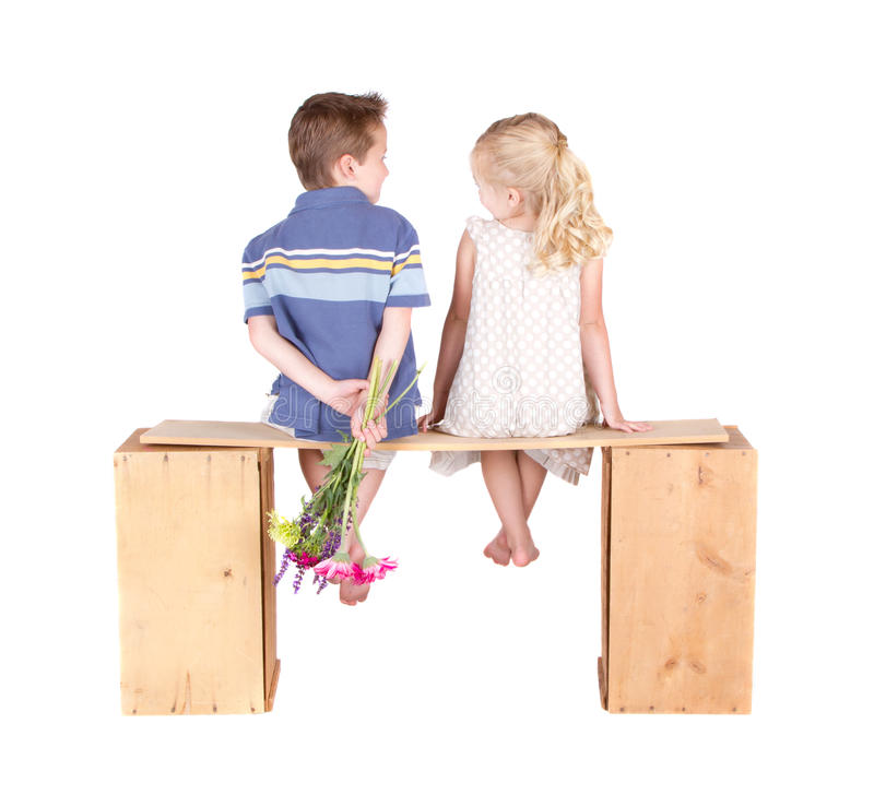 Little girl and boy sitting on a wooden bench stock photos