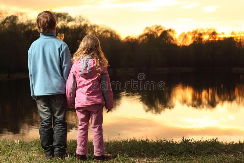 Little girl and boy standing on bank of river. Little girl in pink clothes and boy in blue jacket holding hands and standing back on bank of river and admire on stock photos