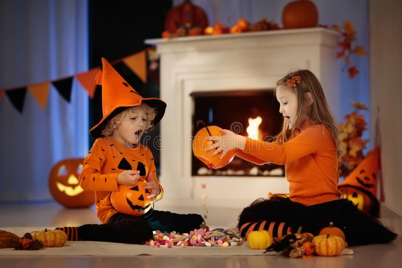 Kids in witch costume on Halloween trick or treat. Little girl and boy in witch costume on Halloween trick or treat. Kids holding candy in pumpkin lantern bucket stock photography