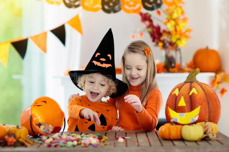 Kids in witch costume on Halloween trick or treat. Little girl and boy in witch costume on Halloween trick or treat. Kids holding candy in pumpkin lantern bucket royalty free stock photography