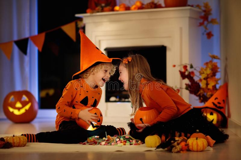 Kids in witch costume on Halloween trick or treat. Little girl and boy in witch costume on Halloween trick or treat. Kids holding candy in pumpkin lantern bucket royalty free stock photos