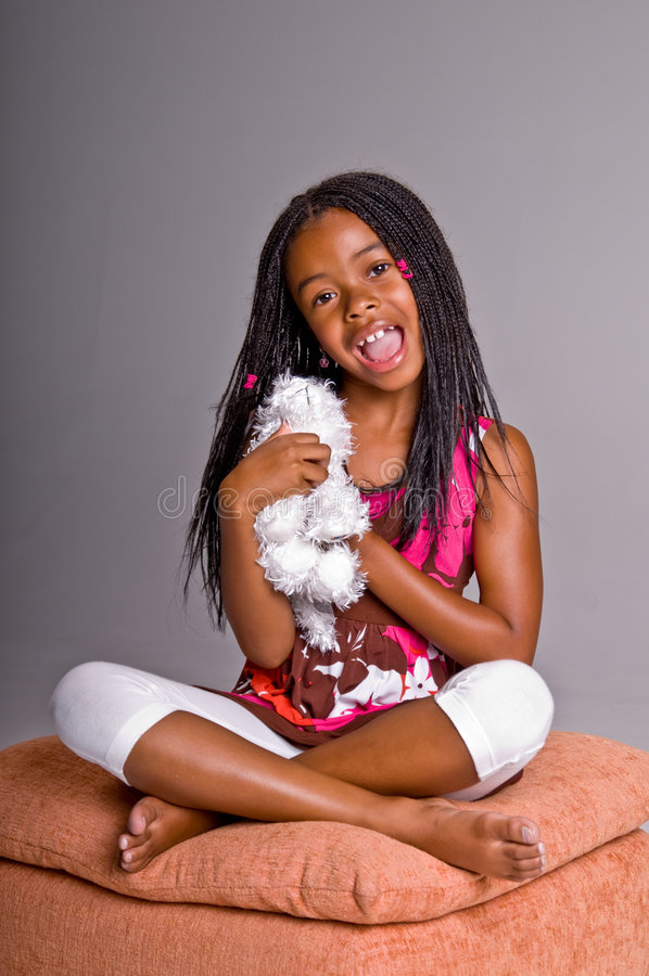 Little Girl With Braids. Little African American girl with finger braids sitting foot stool with her legs crossed with a stuffed puppy stock photo