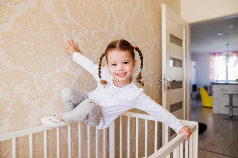 Little girl with braids hanging above white baby crib. Cute little girl with braids hanging above white baby crib royalty free stock images