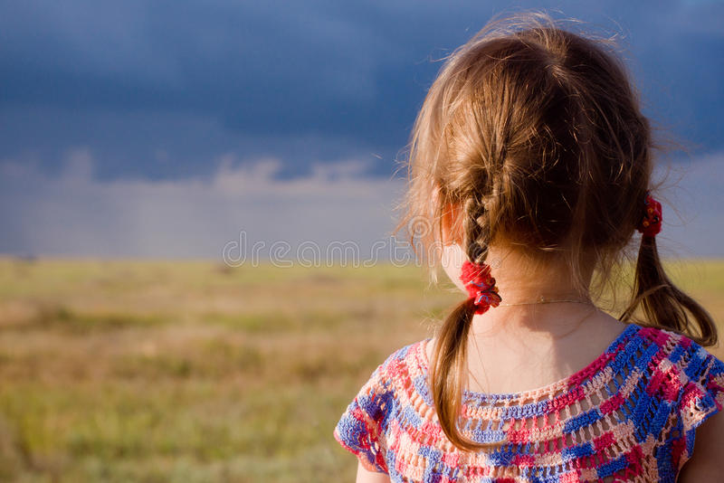 Little girl with braids looking at landscape stock images