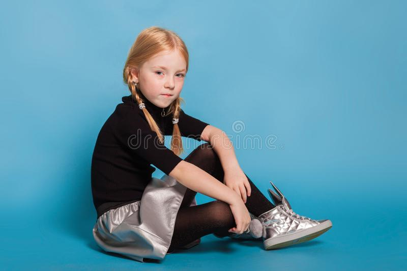 Little girl with braids in stylish clothes on blue background. Isolated on blue, adorable red-haired girl with braids in black sweater with zipper, black tights stock images