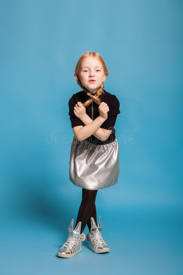 Little girl with braids in stylish clothes on blue background. Isolated on blue, red-haired girl in black sweater with zipper, black tights, silver skirt and stock photography