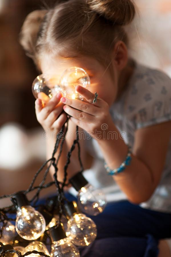 Little girl with bright christmas garland in her hand stock photo