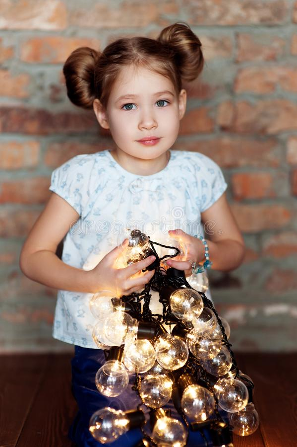 Little girl with bright christmas garland in her hand stock images