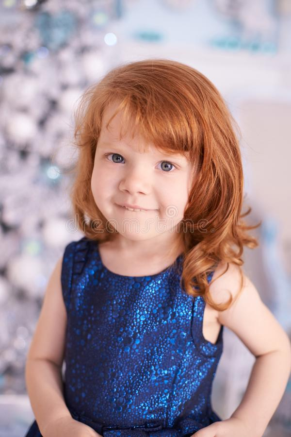 Little girl. Bright interior. Red hair. Vertical stock photography