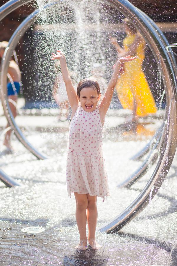 Little girl in a bright sundress rejoices drops of the city fountain. Wet little girl in a bright sundress rejoices drops of the city fountain royalty free stock photos