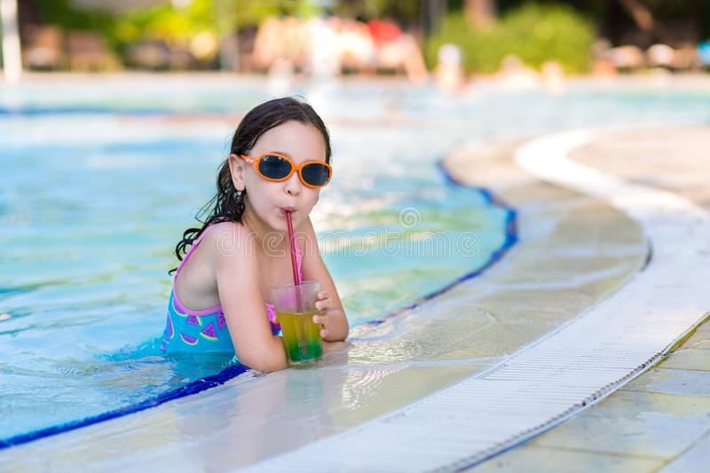 A little girl in a bright swimsuit and sunglasses drinks a cocktail in the pool on sunny summer day, summer vacations stock image