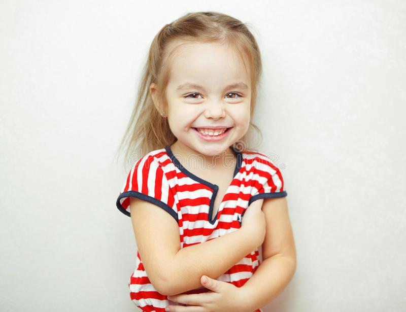 Little girl with broad sincere smile portrait photo. Little girl with broad sincere smile, beautiful brown eyes, nice hairstyle, dressed in striped T-shirt stock images