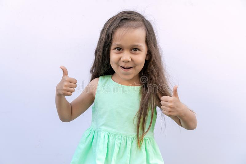 Little girl with brown long curly hair isolated on white background. Kid giving two thumbs up stock image
