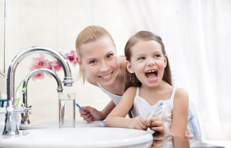 Little girl brushes teeth with her mother royalty free stock image