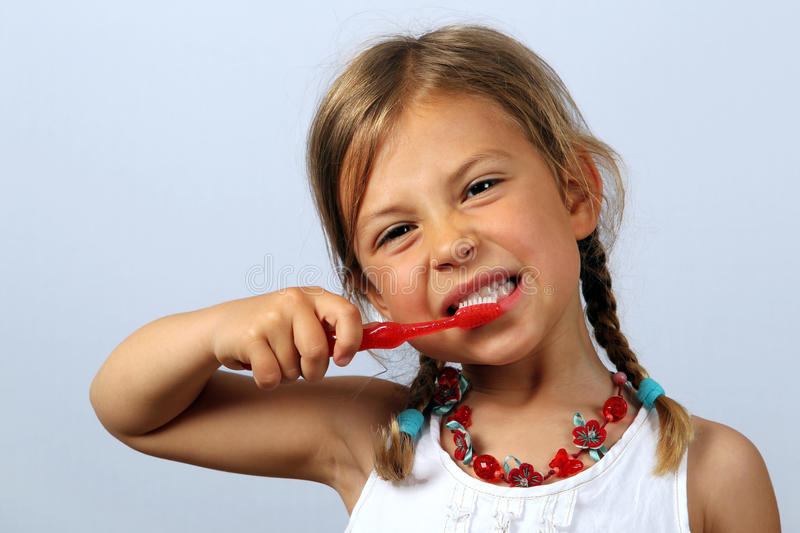 Little girl brushing her teeth. Vigorously with a red toothbrush stock photo