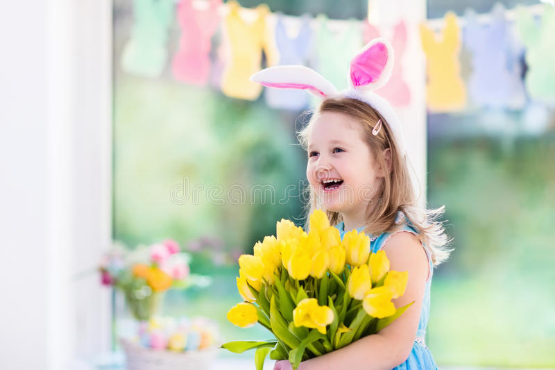 Little girl in bunny ears on Easter egg hunt royalty free stock photography