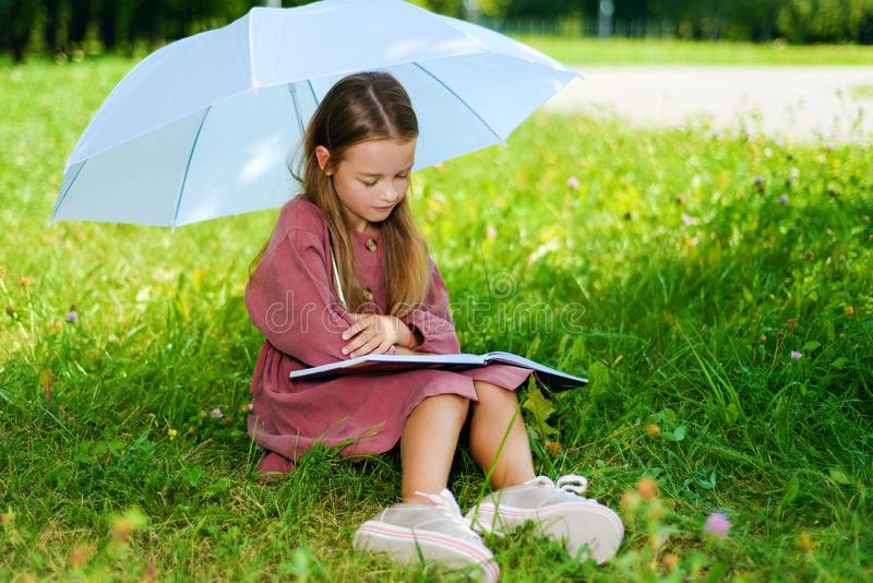 Little girl in dress reading book in park royalty free stock photography