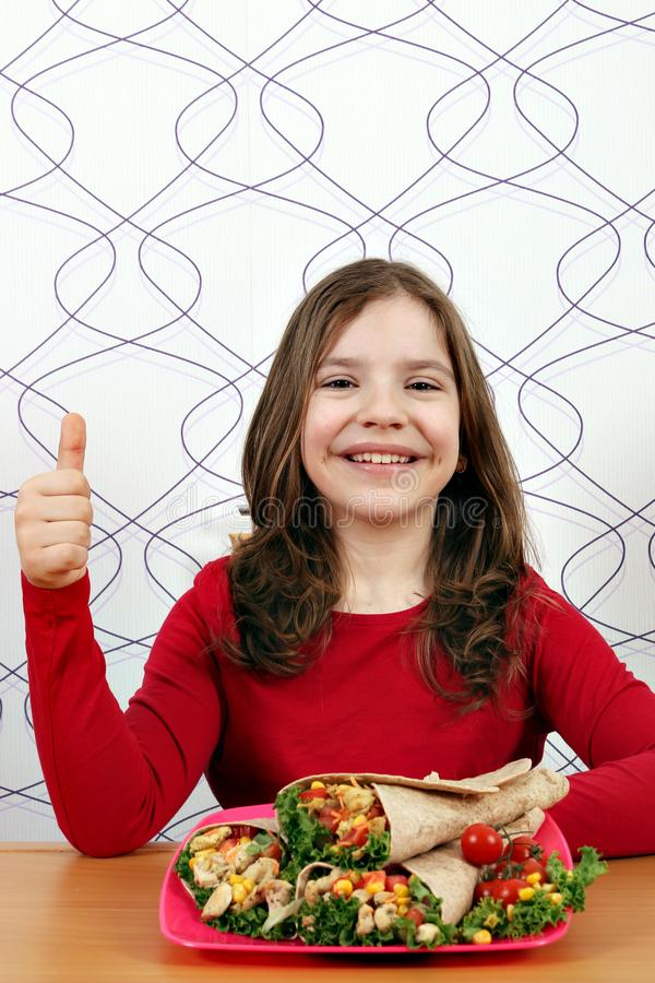 Little girl with burritos and thumb up royalty free stock photography