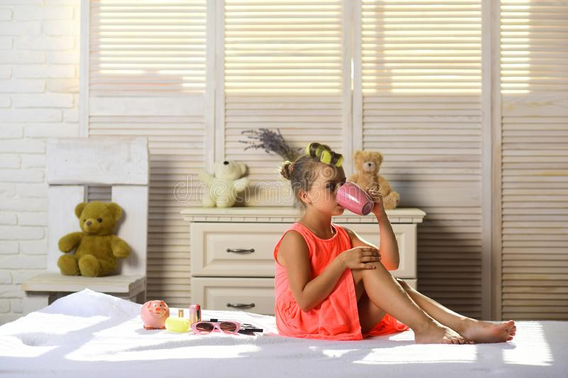 Little girl with calm face drinks tea and plays with cosmetics stock photo