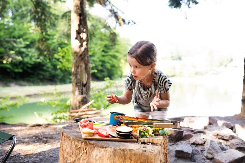 Little girl camping in forest eating grilled food. stock image