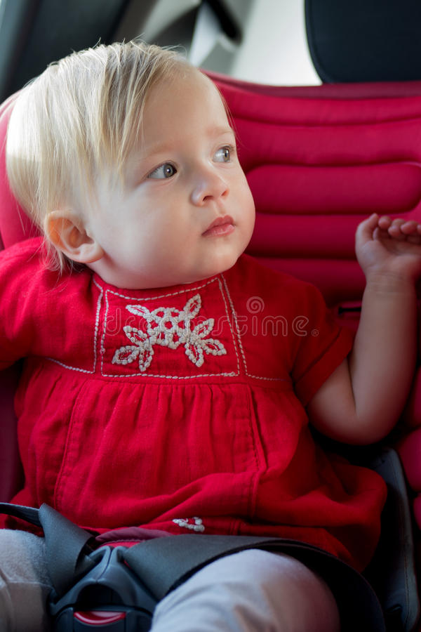 Little girl in car safety seat stock photo