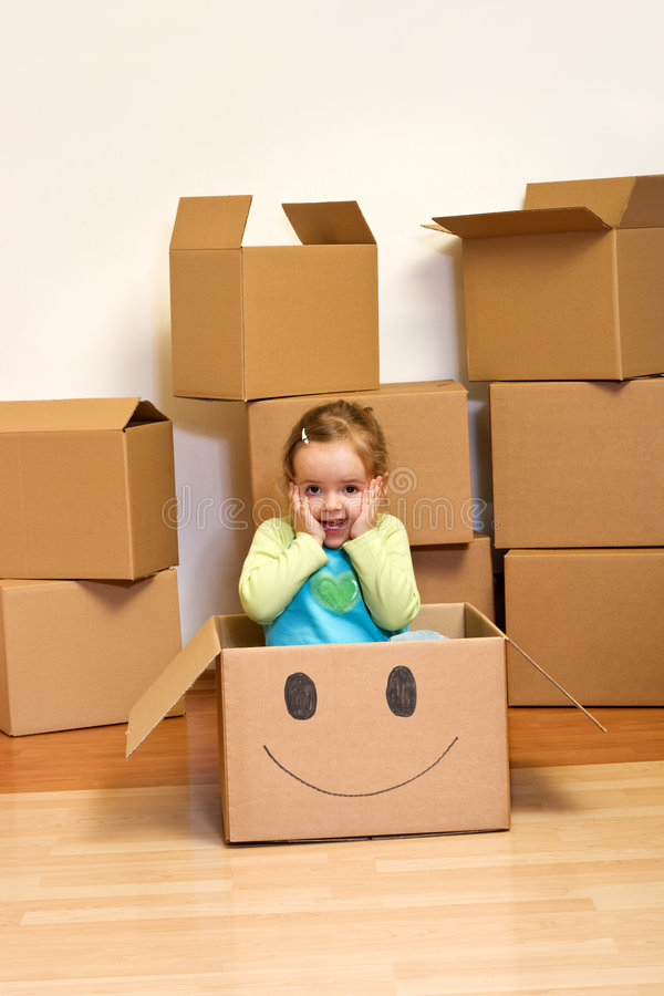 Little girl in cardboard box - moving concept. Little girl in cardboard box with a smiley - moving concept royalty free stock image