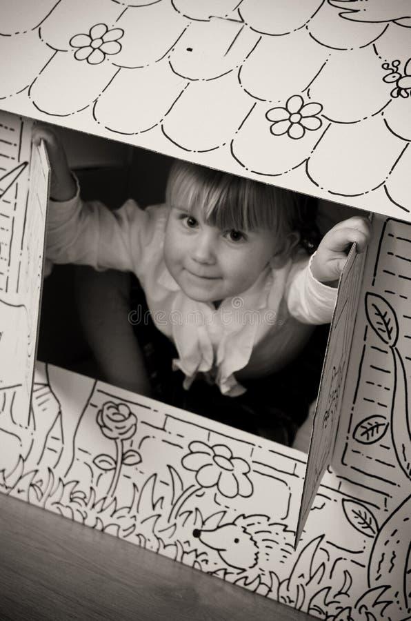Little girl in cardboard house stock photos