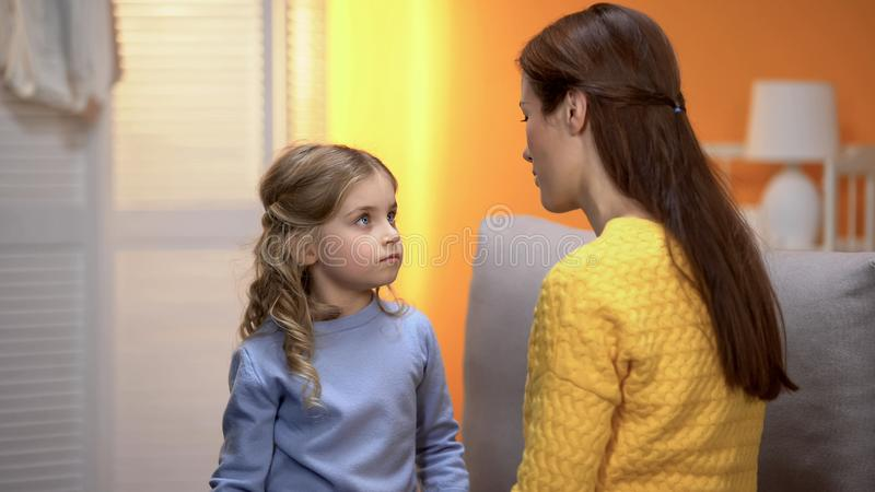Little girl carefully listening to psychologist, kid crisis prevention childcare. Stock photo stock photo