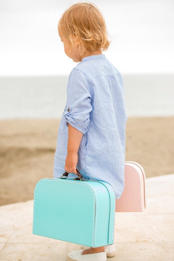 Little girl carrying her suitcases at the seaside stock image