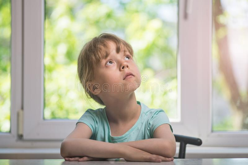 Little girl in casual clothes looking up and thinking. stock photo