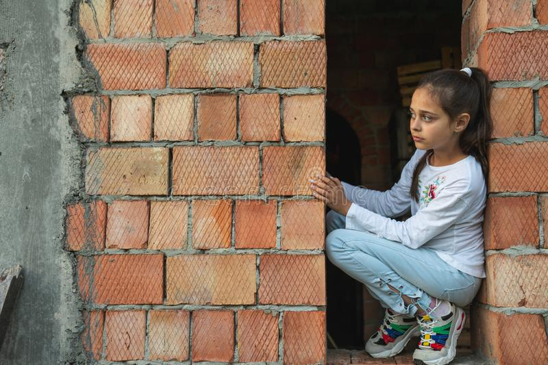 Little girl in casual clothes sitting in the window of an unfinished house with red brick walls, looking away stock photography