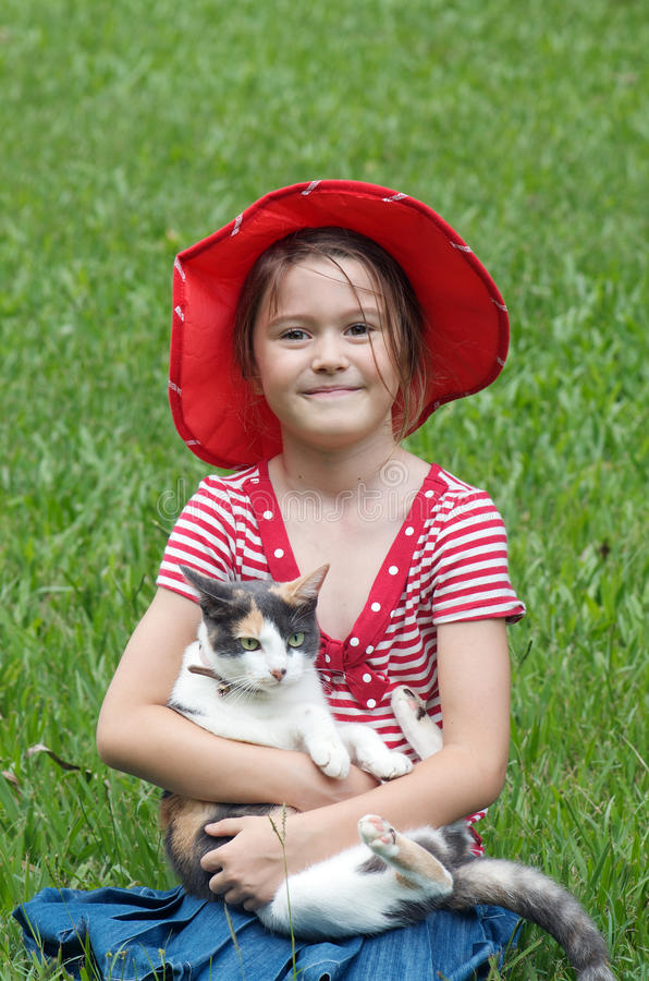Little girl and cat. Pretty little girl wearing red hat sitting on grass with her cute green eyed cat royalty free stock photography