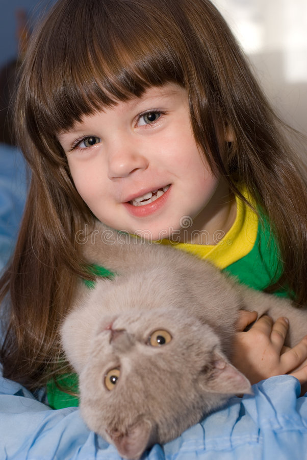 The little girl and cat. The three-year child of the European nationality stock image