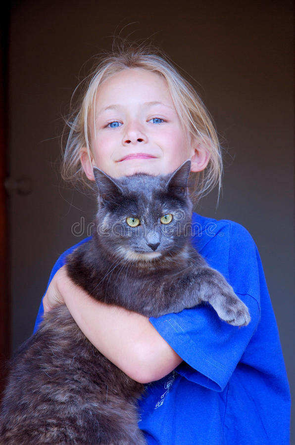 Little girl with cat pet. Portrait of a cute little Caucasian blond girl child with blue eyes holding her cat pet in her arms on black background stock image