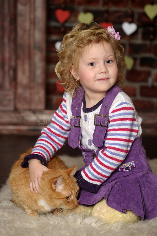 Little girl with cat. Little girl with a red cat royalty free stock photography