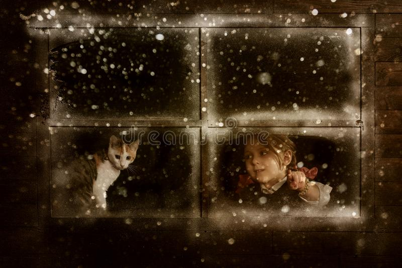 Little girl with a cat watching a snow fall stock photography