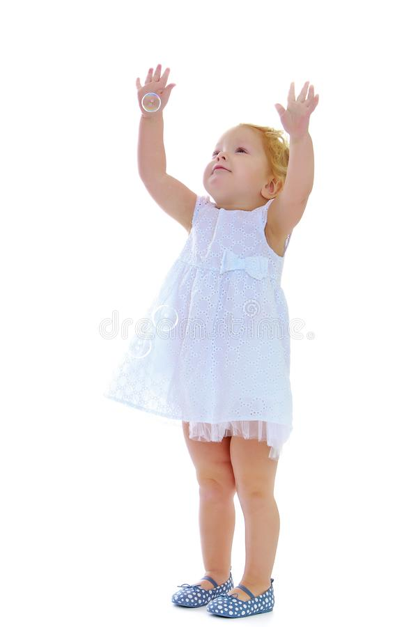 A little girl catches soap bubbles. stock photography
