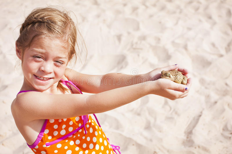 Little Girl Catching A Frog Royalty Free Stock Photography