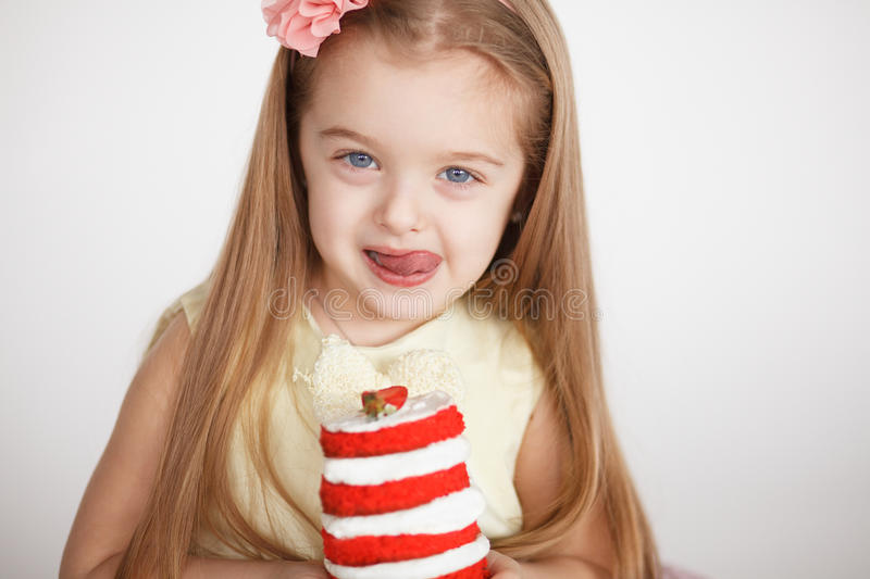 Little girl celebrating a birthday with red cake. Little girl celebrating a birthday with a small red velvet cake. Cute blond preschooler holding beautiful stock photos