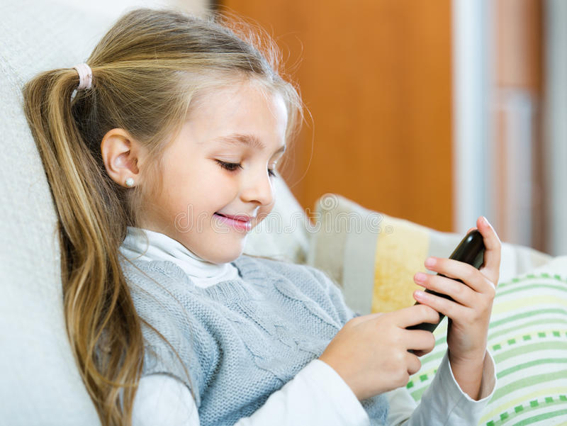 Little girl with cell phone indoors. Cute smiling little girl with long hair having fun with cell phone at home royalty free stock photo